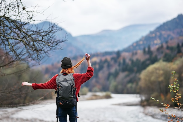 모자, 스웨터, 바지를 입은 여행자가 산의 강둑에서 손으로 몸짓