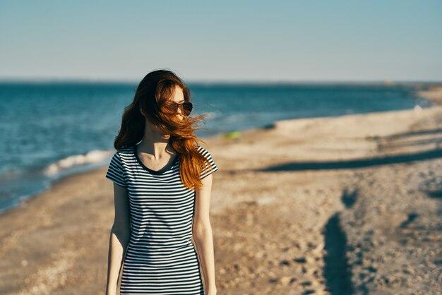 縞模様のtシャツを着た旅行者が夏の山の海の近くのビーチで休んでいます
