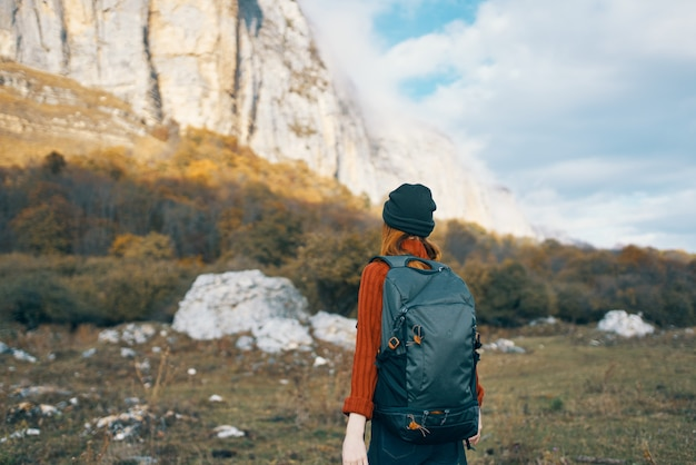 セーターと帽子をかぶった旅行者が自然の中で山で休んでいて、背中にバックパックを背負っています