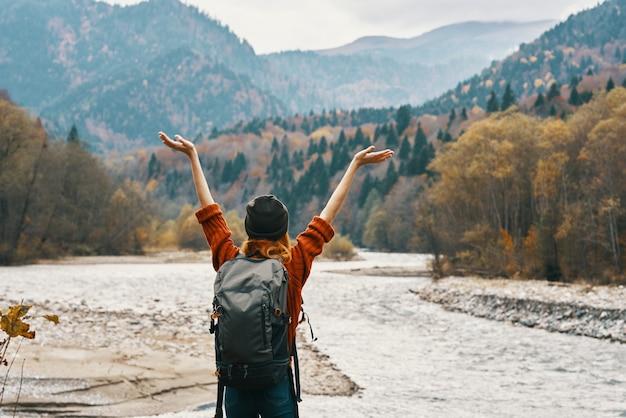 セーターの帽子をかぶった旅行者が、バックパックを手でジェスチャーし、山の川岸でリラックスします。