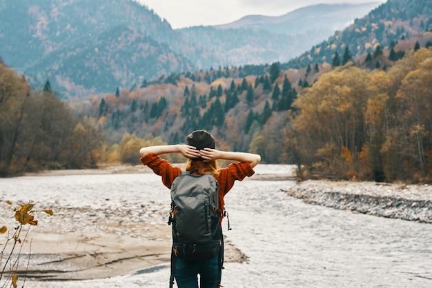 セーターの帽子をかぶった旅行者が、バックパックを手でジェスチャーし、川岸でリラックスします。