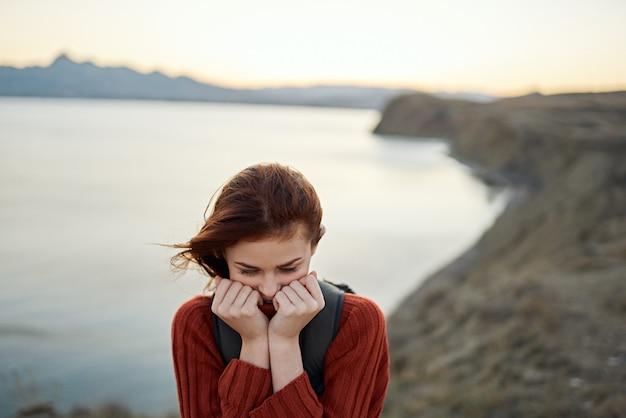 セーターを着た旅行者は、山のトップビューバックパックオーシャンツーリズムの自然に彼女の顔の近くで彼女の手を握ります