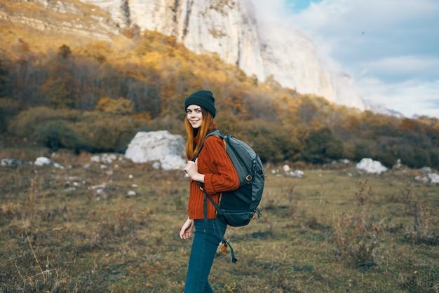 背中にバックパックと暖かい帽子の山の秋の風景とセータージーンズの旅行者。高品質の写真