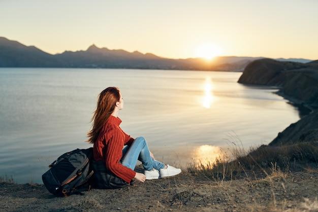 セーターを着た旅行者が海の近くの山の地面に座って夕日を眺める