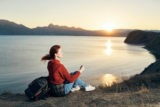 스웨터를 입은 여행자가 바다 근처 산의 땅에 앉아 일몰을 바라 봅니다.