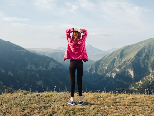 Путешественник в леггинсах, кроссовках и куртке отдыхает в горах на природе. фото высокого качества