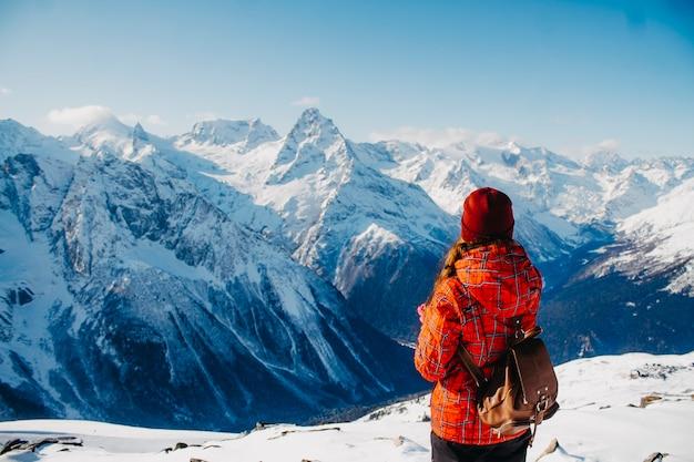 심연의 가장자리에있는 여행자가 멀리서 눈 덮인 산을 들여다 봅니다.