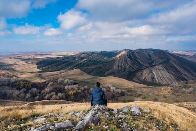 Путешественник сидит на холме и небольшой горе осенью и смотрит вдаль