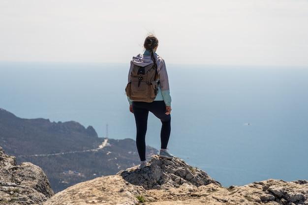 バックパックを背負った旅行者は、旅行とアウトドアのコンセプトを非常に高いところから海の景色を眺めています...