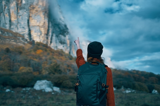 バックパックと赤いセーターを着た旅行者は、彼女の手と青い空で山を示しています