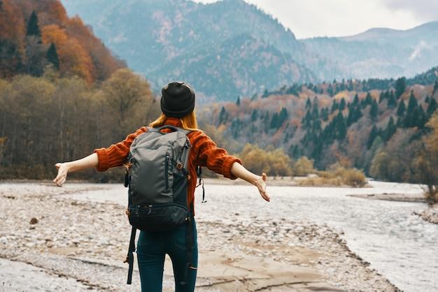 セーターとジーンズにバックパックを持った旅行者は、近くの自然の山で休んでいます。