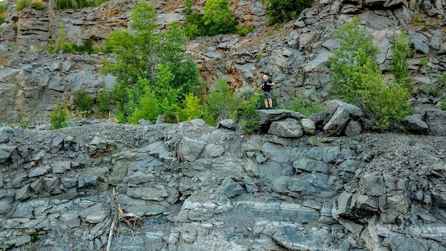 肩にバックパックを背負った旅行者が石の崖の破損の近くに立っています。