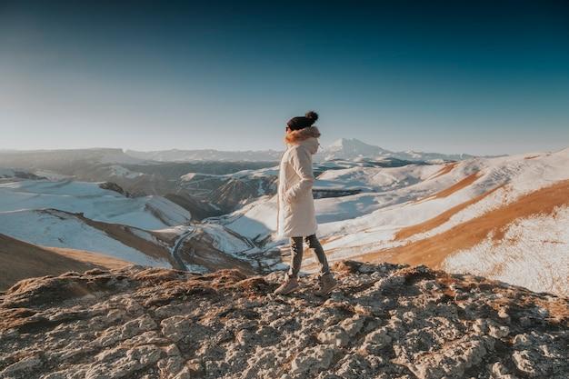 배낭을 든 여행자가 겨울에 산을 걷는다. 산 등반 사진.