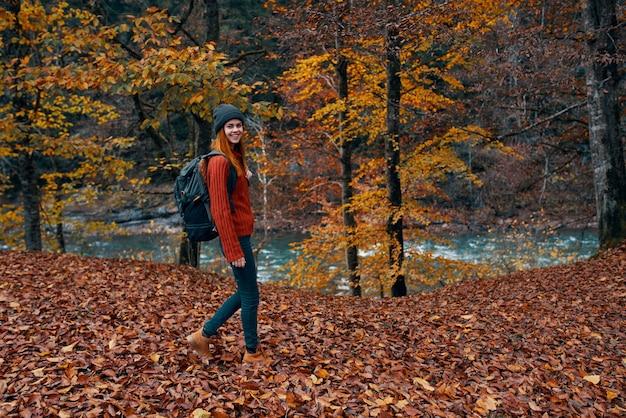 バックパックを背負った旅行者が、秋の川の近くの自然の公園を散歩する