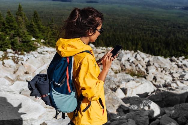 Путешественник с телефоном, крупный план. девушка-туристка в желтой куртке с рюкзаком держит в руках телефон. пешие прогулки женщина с помощью смарт-телефона, путешествий и концепции активного образа жизни. копировать пространство