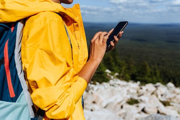 Путешественник с телефоном, крупным планом. молодая женщина в желтой ветровке использует поисковую карту смартфона на фоне сельской местности. взрослая женщина, держащая и использующая смартфон. путешествия и активный образ жизни