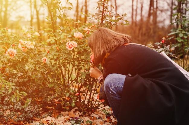 Женщина-путешественница в модной осенней одежде нюхает розовые цветы в осеннем парке. концепция местного путешествия. вспышка