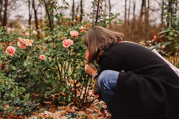 Женщина-путешественница в модной осенней одежде нюхает розовые цветы в осеннем парке. концепция местного путешествия