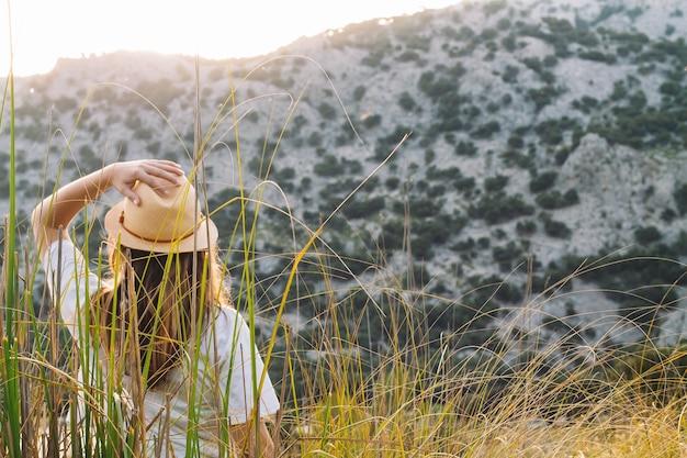 Путешествующая девушка в шляпе перед горой