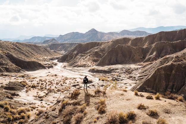Путешественник гуляет тропами огромной пустыни в солнечный день - фото пейзажа