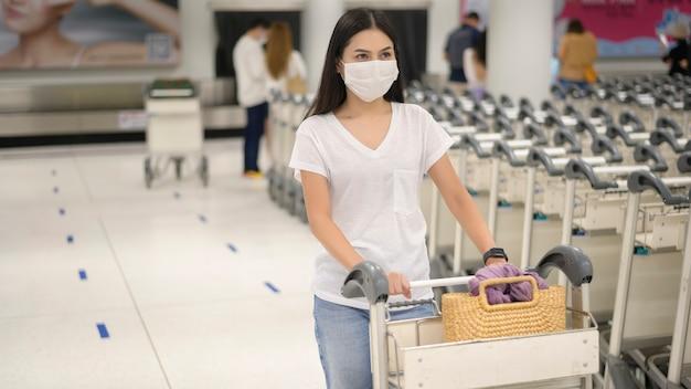 트롤리에 수하물이있는 공항에서 보호 마스크를 착용 한 여행 여성, covid-19 대유행, 안전 여행, 사회적 거리두기 프로토콜, 새로운 일반 여행 컨셉