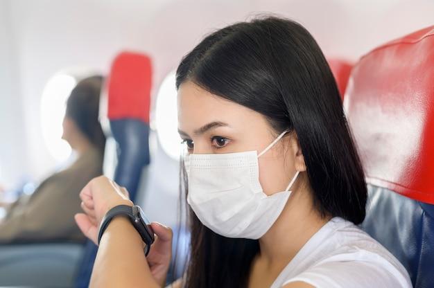 스마트 시계를 사용하여 기내에서 보호 마스크를 착용 한 여행 여성, covid-19 대유행, 안전 여행, 사회적 거리두기 프로토콜, 새로운 일반 여행 컨셉