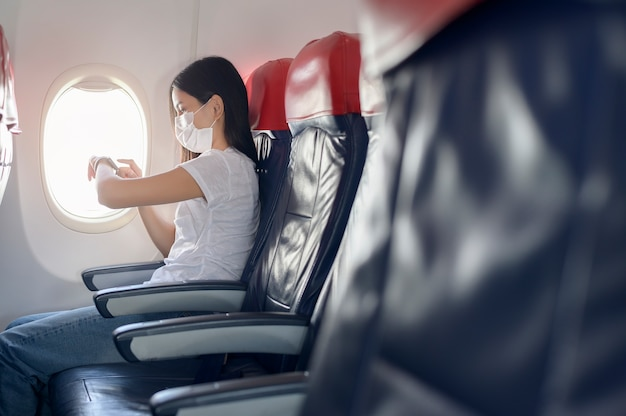 Путешествующая женщина в защитной маске на борту самолета с использованием умных часов, путешествие в условиях пандемии covid-19, безопасные поездки, протокол социального дистанцирования, новая концепция нормального путешествия