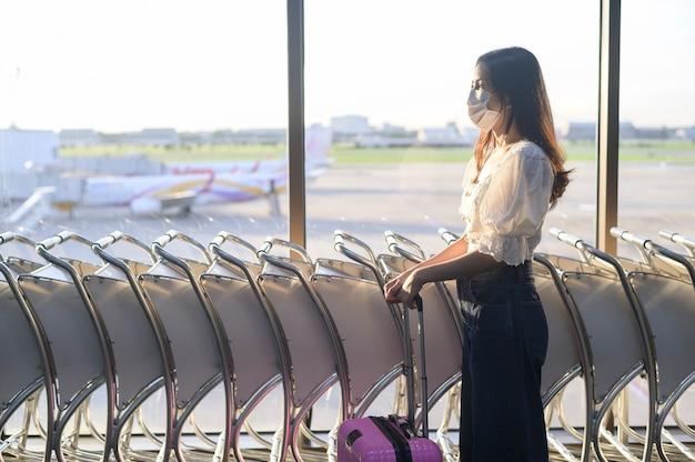 旅行者の女性は国際空港で防護マスクを着用し、covid-19パンデミック下で旅行、安全旅行、社会的距離のプロトコル