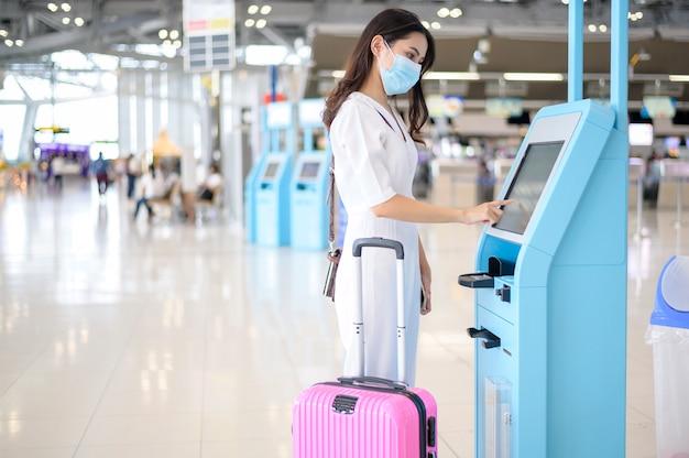 旅行者の女性は国際空港で防護マスクを着用し、covid-19パンデミック下で旅行し、