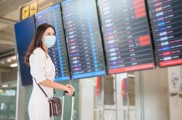 Женщина-путешественница в защитной маске в международном аэропорту, путешествующая в условиях пандемии covid-19,