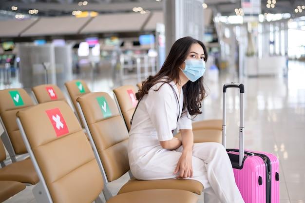 여행자 여성이 국제 공항에서 보호 마스크를 쓰고 코로나 19 유행에 걸렸고,