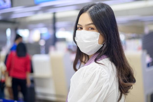 旅行者の女性が国際空港で保護マスクを着用し、covid-19パンデミックの下で旅行