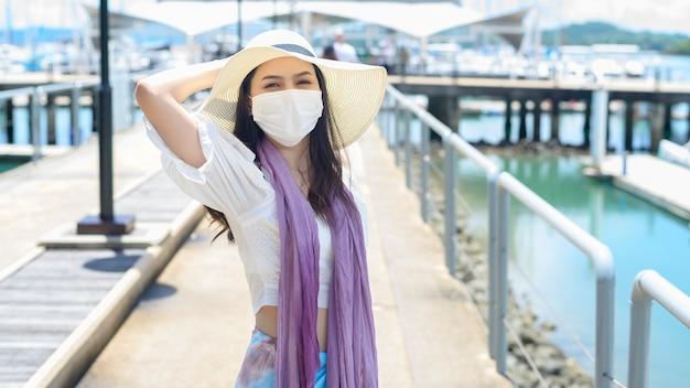 旅行者の女性がドックで防護マスクを着ています