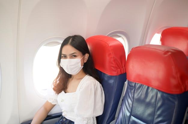 여행하는 여성이 기내에서 보호 마스크를 착용하고 있으며, covid-19 대유행, 안전 여행, 사회적 거리두기 프로토콜에 따라 여행합니다.