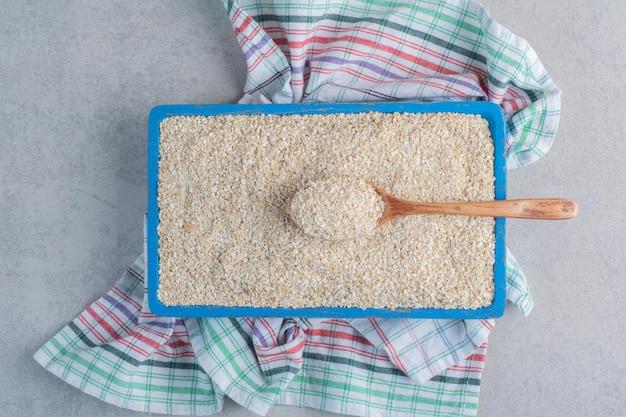 Поднос, полный риса на полотенце на мраморной поверхности