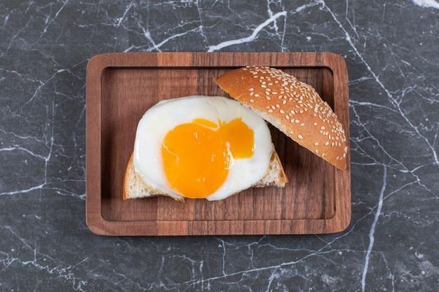 Поднос с жареным яйцом и нарезанной булочкой.
