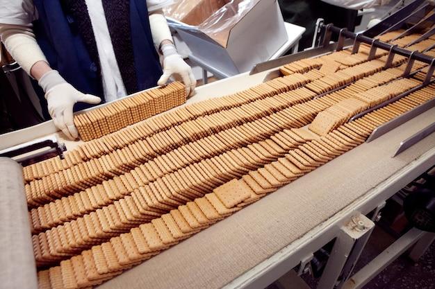 빵집의 컨베이어 벨트에서 기성품 쿠키 트레이를 가져옵니다.