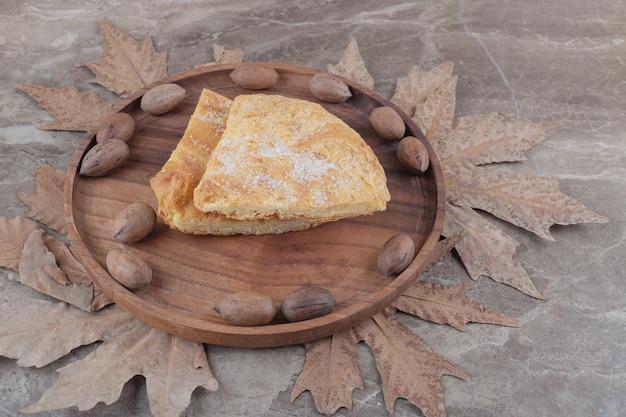 ピーカンナッツと大理石のフェセリフラットブレッドのスライスが入ったトレイ 無料写真