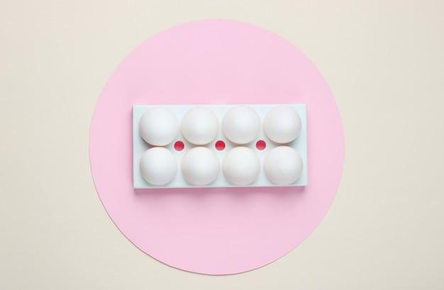 真ん中にパステルピンクの円が入ったベージュの白い鶏の卵が入ったトレイ。