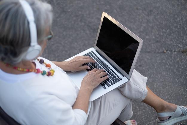 랩톱 컴퓨터를 사용하여 공원 벤치에 앉아 트렌디한 비즈니스 수석 여자. 그녀는 헤드폰을 끼고 야외에서 일한다