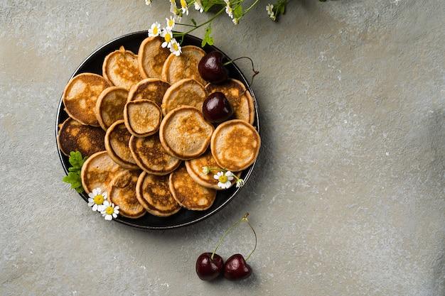 小さなパンケーキをクローズアップしたトレンディな自家製朝食。テーブルの上のミニパンケーキ、チェリー、お茶。水平方向