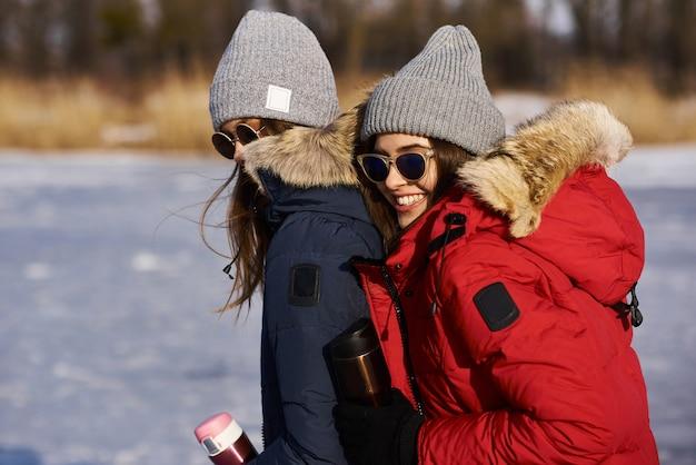 トレンディな若い女の子が歩いて、冬に屋外で楽しんでいます。