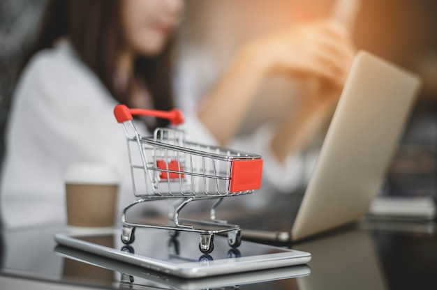 Тележка на экране планшета. идеи об онлайн-покупках. девушка использует телефон, чтобы напрямую покупать товары у продавца через интернет. концепция шопоголика онлайн