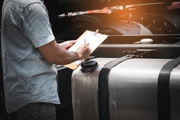 セミトラックの大型燃料タンクの安全性を検査するクリップボードを持ったトラック運転手。
