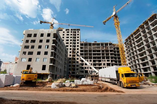 Грузовик стоит на фоне строящегося нового дома