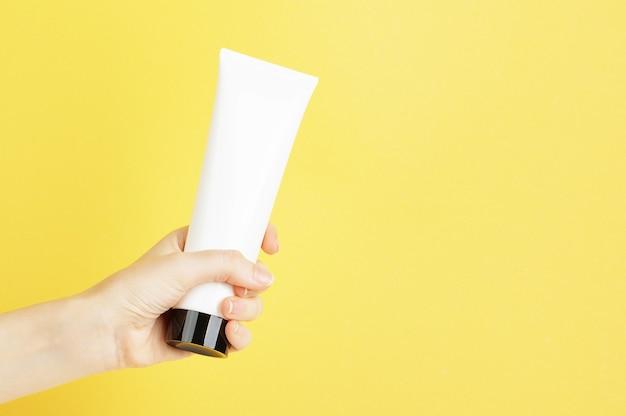 흰색 패키지에 검은색 캡이 있는 크림 튜브가 노란색 배경에 있는 여성의 손에 있습니다. 플라스틱 용기에 로션, 바디 크림, 스킨 케어. 조롱하고 공간을 복사합니다. 여름 스킨케어 개념입니다.