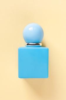 パステルイエローに丸いキャップが付いたターコイズの香水瓶