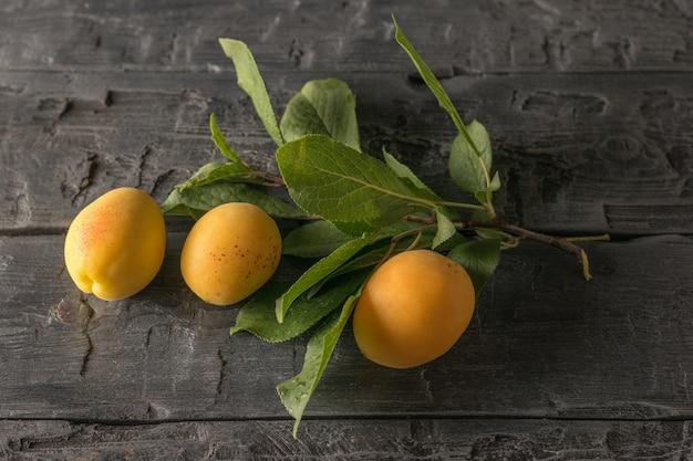 緑の葉と熟したアプリコットの果実が木製のテーブルにある小枝