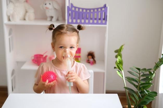2歳の子供が吸入マスクに息を吹き込みます。