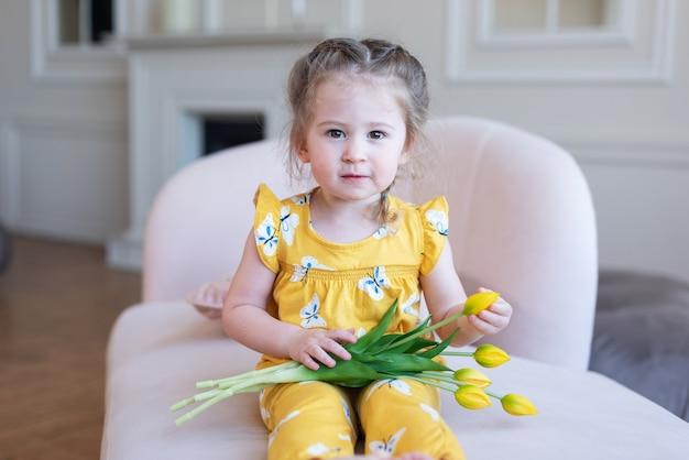 Двухлетняя милая красивая девушка в желтом костюме сидит на диване и держит в себе желтые тюльпаны